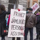 Bild från en demonstration. En person står med ryggen mot kameran och håller i en skylt där det står: Frihet, jämlikhet, personlig assistans